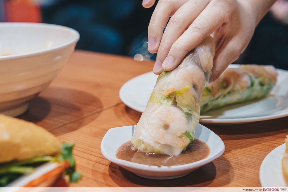 Dipping a fresh spring roll into chilli