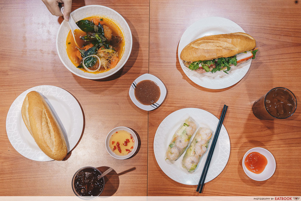 Flatlay comprising banh mi, fresh spring rolls and beef stew
