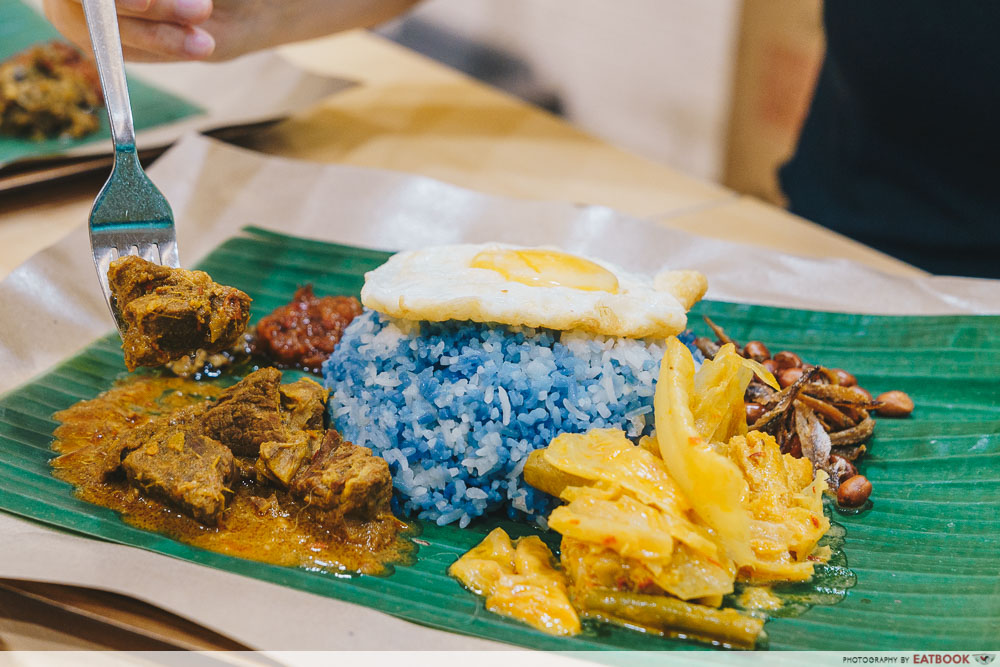 Nasi lemak with blue rice and a sunny side up egg on top