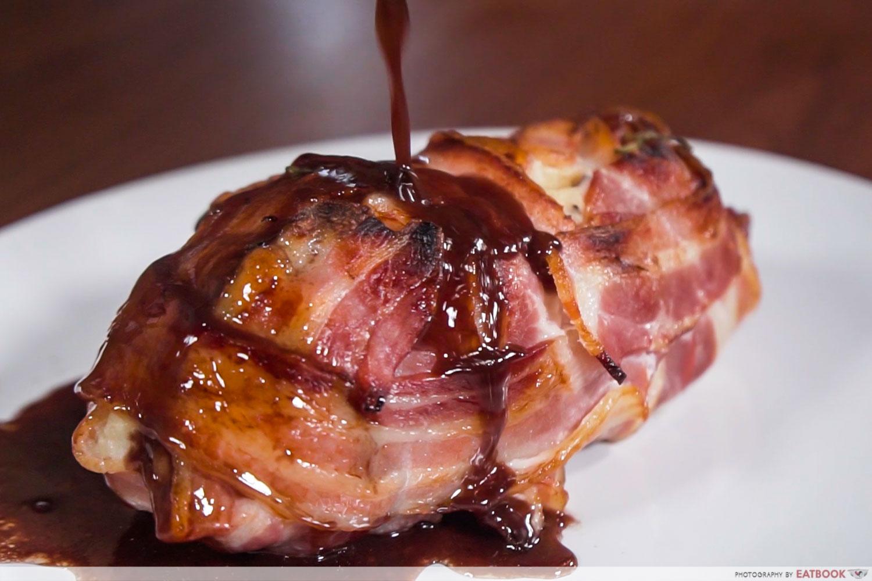 Gotcha Pork Roast - Pouring of red wine based sauce on pork roast